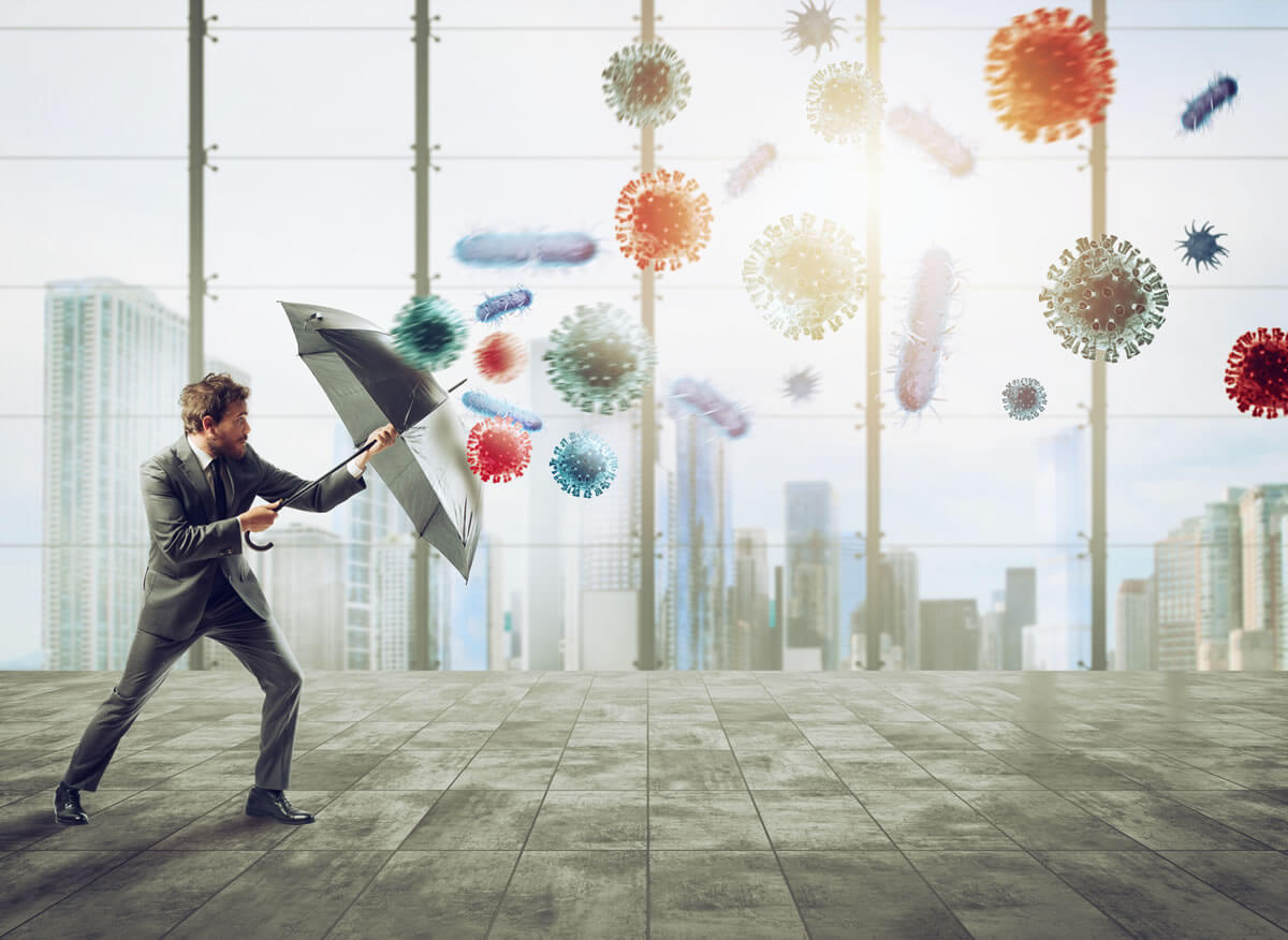 Man using an umbrella to protect against COVID molecules represents COVID proofing