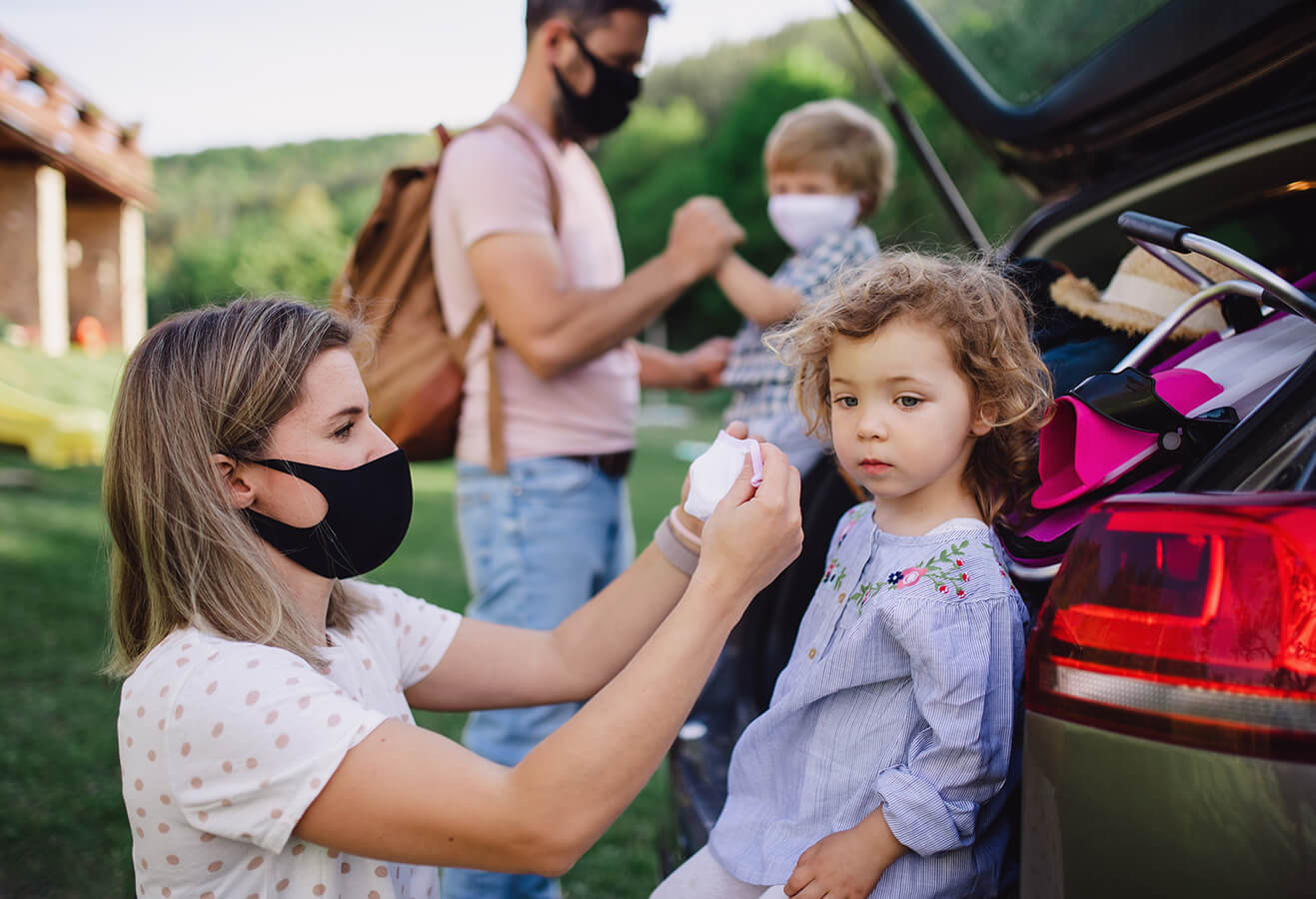 Young family putting on masks as a COVID safety measure